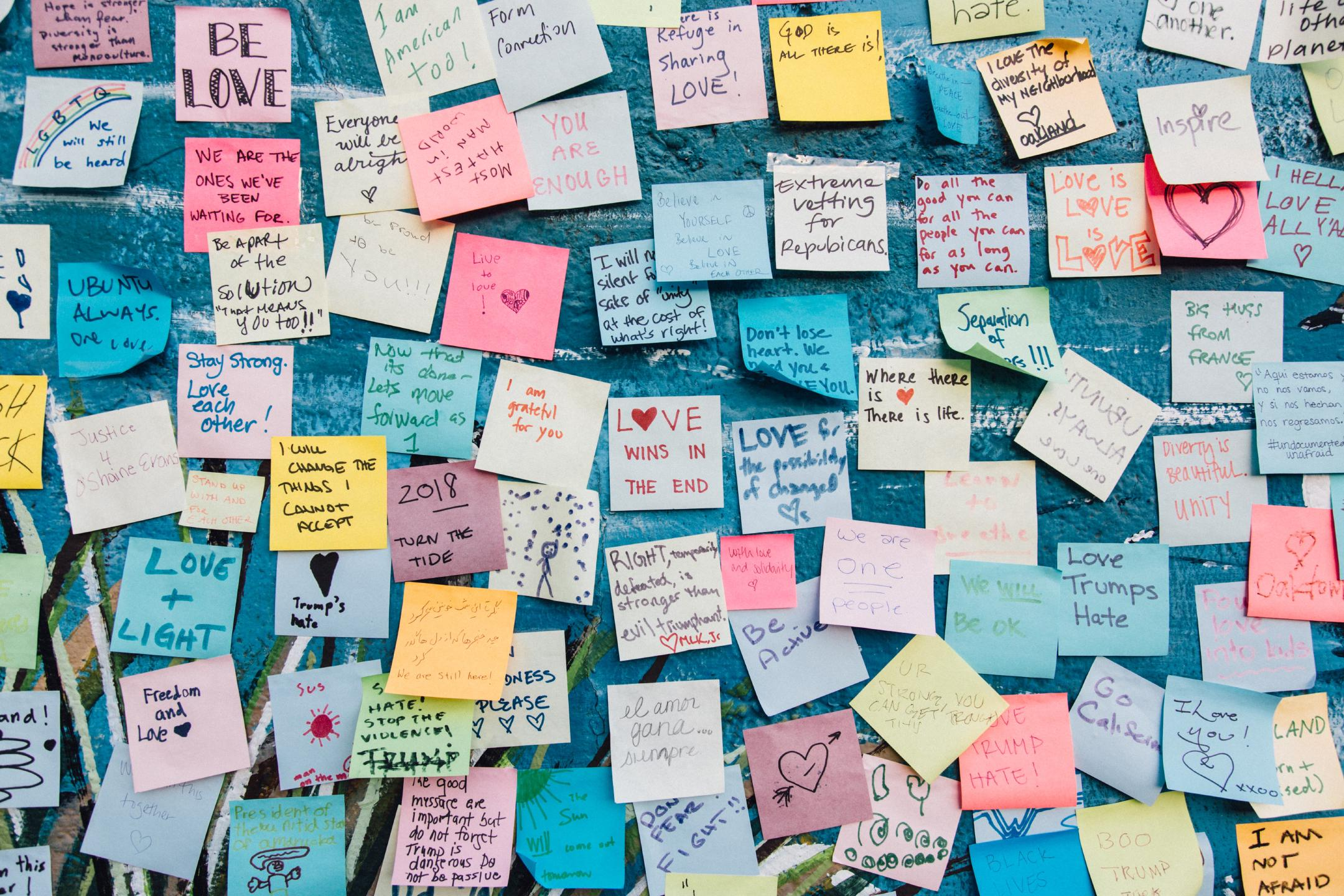 a wall full of colorful post-it notes with various pro-love anti-hate messages